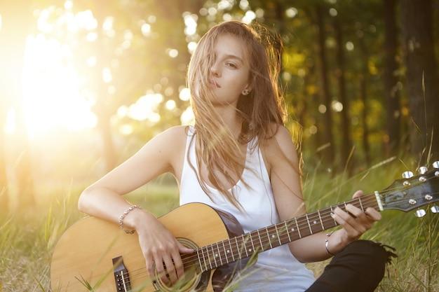 Junge frau, die gitarre in der natur während des sonnenuntergangs spielt