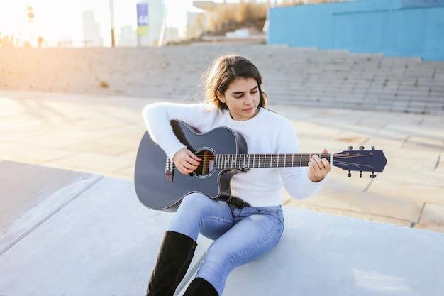 Junge frau, die gitarre spielt