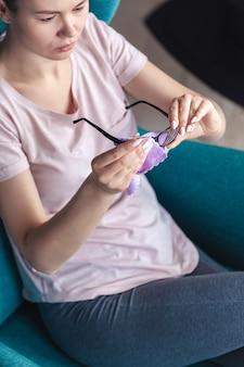 Junge frau, die gläser mit einer serviette reinigt, während sie in einem ch sitzt