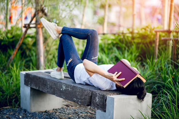 Junge frau, die glücklich das buch in der natur liest