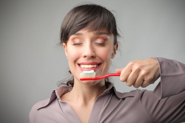 Junge frau, die glücklich eine zahnbürste hält