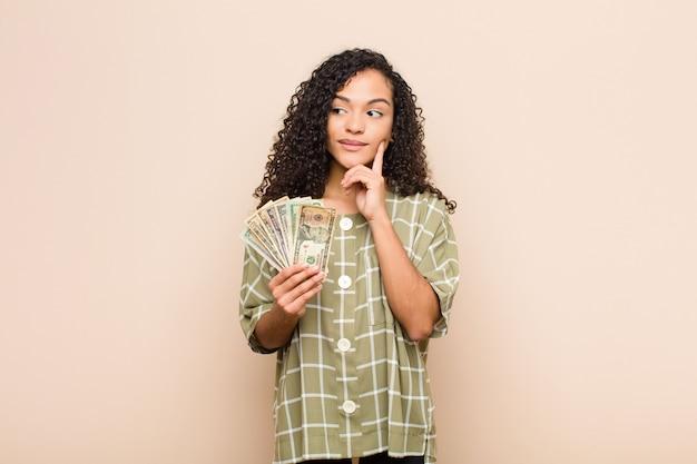 Junge frau, die glücklich lächelt und tagträumen oder zweifel hat und zur seite schaut, die dollar-banknoten hält