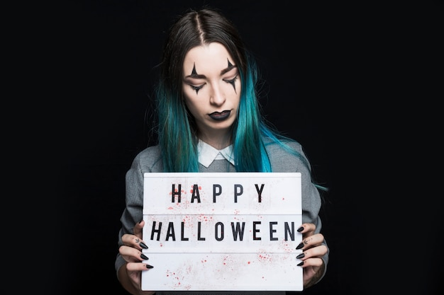 Junge frau, die glückliche halloween-aufschrift zeigt