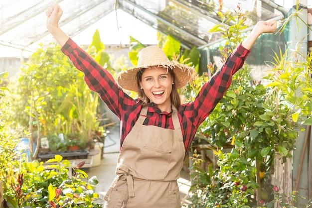 Junge frau, die glücklichen landwirtschaftlichen frauenarbeiter im gewächshaus lächelt. kleinunternehmen. farmer friendly freut sich über die errungenschaft des geschäfts