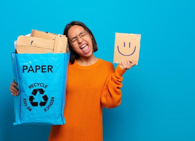 Junge frau, die glückliches gesicht recycelt und hält