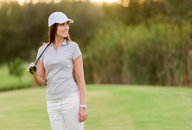 Junge frau, die golf spielt