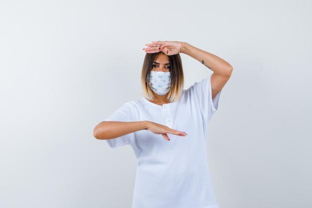 Junge frau, die größenzeichen in t-shirt, maske und selbstbewusstsein, vorderansicht zeigt.