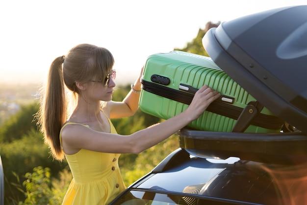 Junge frau, die grünen koffer aus autodachträger herausnimmt. reise- und urlaubskonzept.