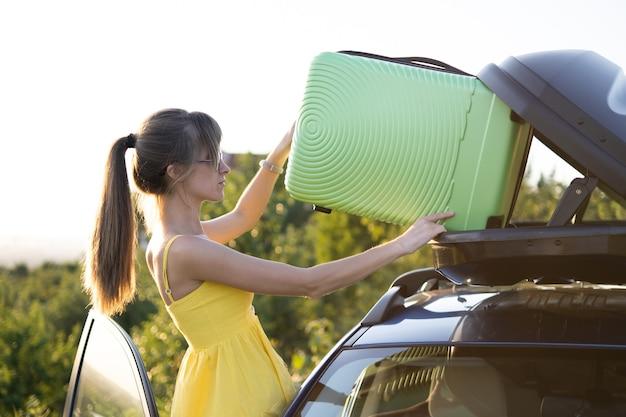 Junge frau, die grünen koffer in autodachgepäckträger einsetzt. reise- und urlaubskonzept.