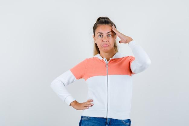 Junge frau, die grußgeste zeigt, hand auf hüfte in reißverschluss-kapuzenpulli, jeans hält und zuversichtlich schaut
