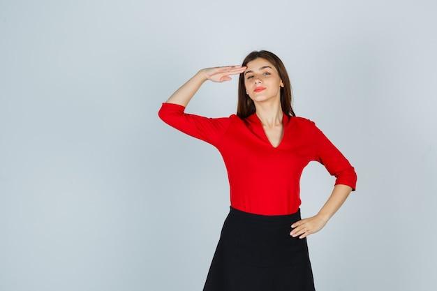 Junge frau, die grußgeste zeigt und hand auf hüfte in roter bluse hält