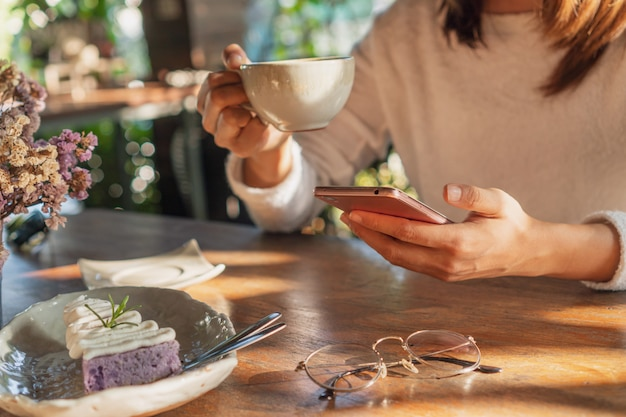 Junge frau, die gute nachrichten auf handy während der ruhe im kaffeehaus liest, glückliche asiatische frau, die ihr foto auf smartphone beim trinken des kaffees im café während der freizeit beobachtet.