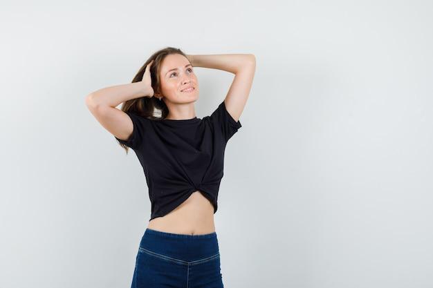 Junge frau, die haare mit händen in der schwarzen bluse, in den hosen hält und fröhlich schaut.