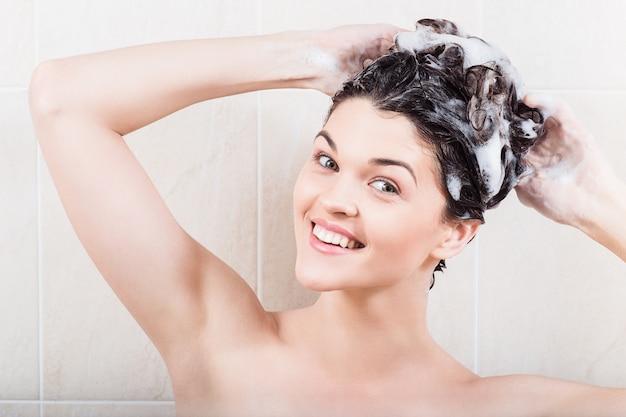 Junge frau, die haare mit shampoo in der dusche wäscht