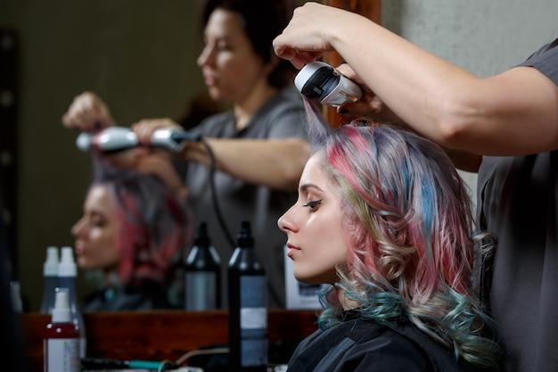 Junge frau, die haarfarbe und frisur im salon färbt.