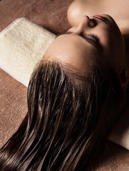 Junge frau, die haarpflegeverfahren im spa-salon erhält. schönheitsbehandlung. spa-salon