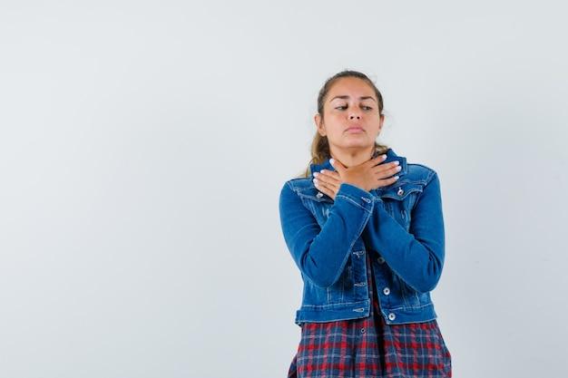 Junge frau, die hände am hals im hemd, in der jacke und im verärgerten blick gekreuzt hält. vorderansicht.