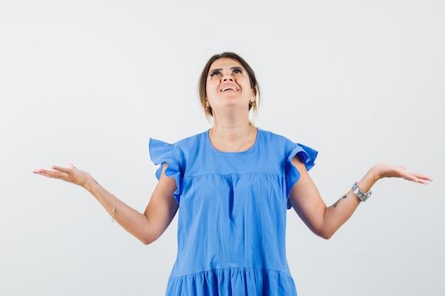 Junge frau, die hände anhebt, während sie im blauen kleid nach oben schaut und dankbar schaut