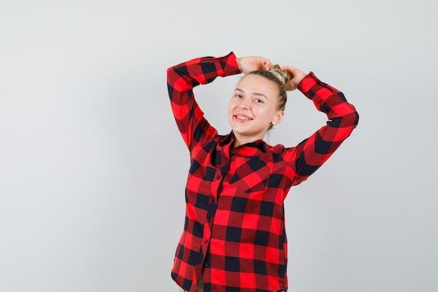 Junge frau, die hände auf haar im karierten hemd hält und verspielte vorderansicht schaut.