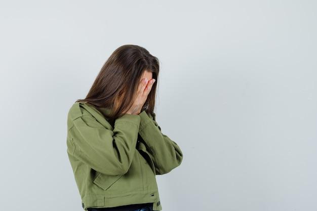 Junge frau, die hände auf ihrem gesicht in grüner jacke bedeckt und traurige vorderansicht schaut. platz für text