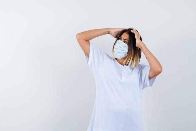 Junge frau, die hände auf kopf im t-shirt, in der maske und im zögernden blick, vorderansicht hält.