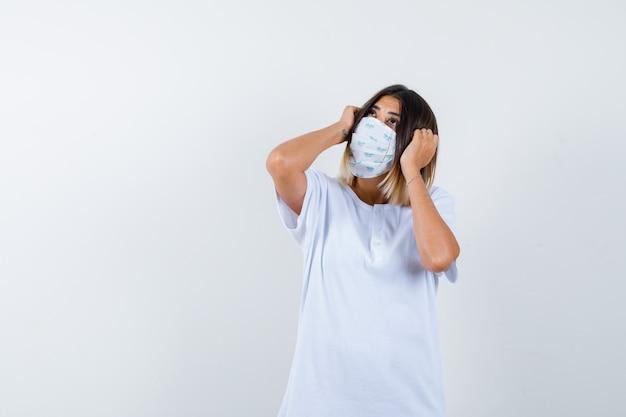 Junge frau, die hände auf kopf in t-shirt, maske und nachdenklich aussehend hält. vorderansicht.