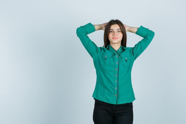 Junge frau, die hände hinter dem kopf im grünen hemd, in den hosen und in der ansicht des stolzen vorderansicht hält.