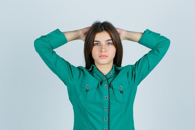 Junge frau, die hände hinter kopf im grünen hemd hält und stolz, vorderansicht schaut.