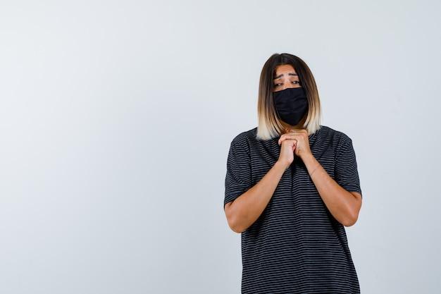 Junge frau, die hände in betender position im schwarzen kleid, in der schwarzen maske und in der fokussierten vorderansicht fasst.