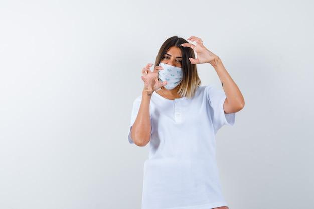 Junge frau, die hände in der aggressiven weise im t-shirt, in der maske und im gestressten blick, vorderansicht hält.