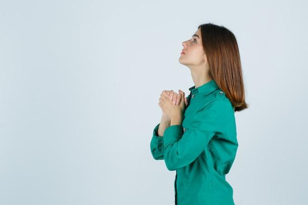 Junge frau, die hände in der gebetsgeste im grünen hemd fasst und hoffnungsvoll schaut.