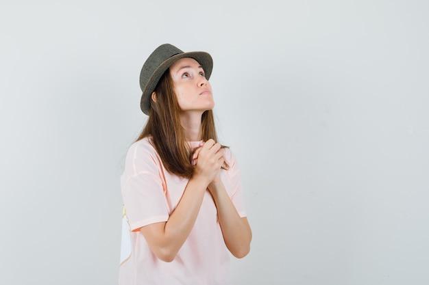 Junge frau, die hände in der gebetsgeste im rosa t-shirt, im hut und im hoffnungsvollen blick fasst. vorderansicht.