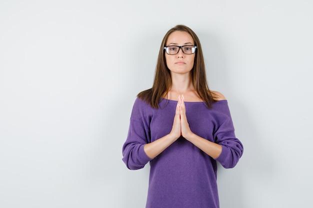 Junge frau, die hände in der gebetsgeste im violetten hemd hält und ruhig, vorderansicht schaut.