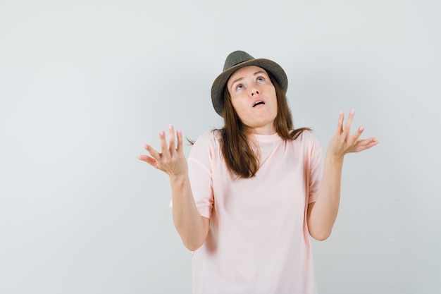 Junge frau, die hände in fragender weise in rosa t-shirt, hutvorderansicht erhebt.