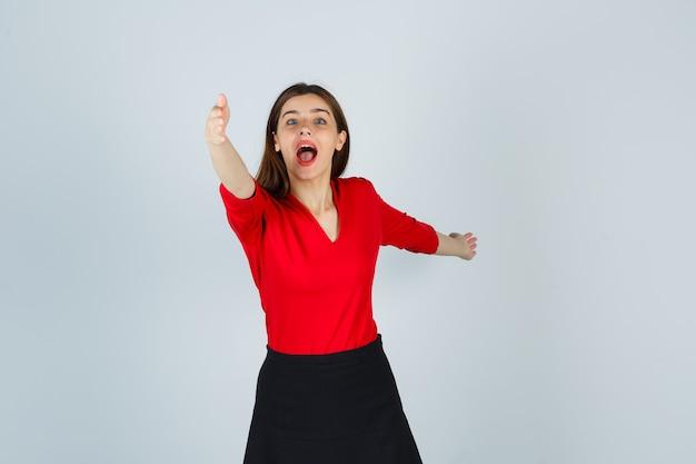Junge frau, die hände in richtung kamera in roter bluse, schwarzem rock streckt und aufgeregt schaut