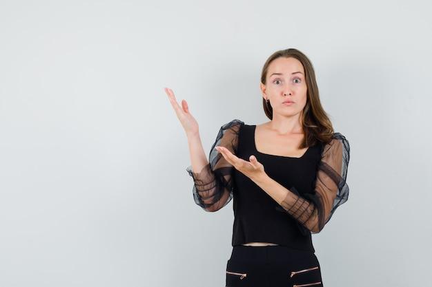 Junge frau, die hände oben links in der schwarzen bluse und in der schwarzen hose streckt und überrascht aussieht. vorderansicht.