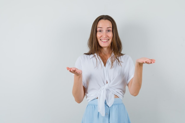 Junge frau, die hände streckt, um etwas in der weißen bluse und im hellblauen rock zu erhalten und fröhlich auszusehen