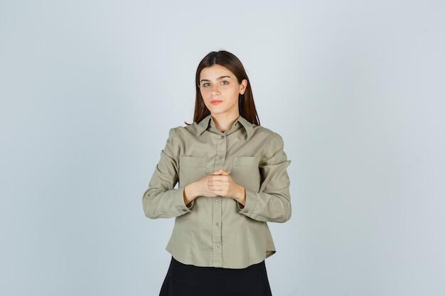 Junge frau, die hände über brust in hemd, rock hält und vernünftig aussieht