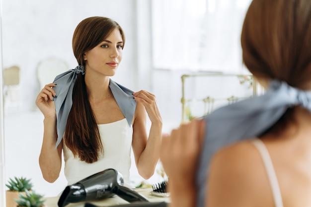 Junge frau, die häusliche kleidung mit pferdeschwanz trägt, die ihr spiegelbild in den spiegel schaut und eine schleife im badezimmer bindet. frisurenkonzept