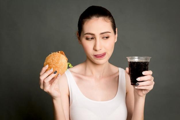 Junge frau, die hamburger und cola auf grauem hintergrund isst