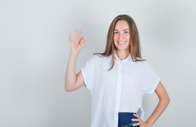 Junge frau, die hand anhebt und im weißen t-shirt lächelt