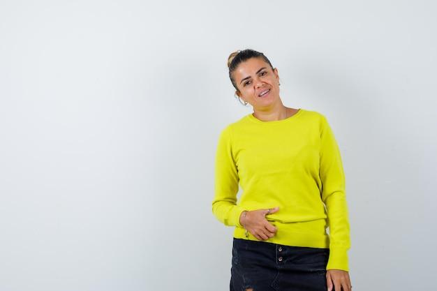 Junge frau, die hand auf bauch in pullover, jeansrock hält und fröhlich aussieht looking