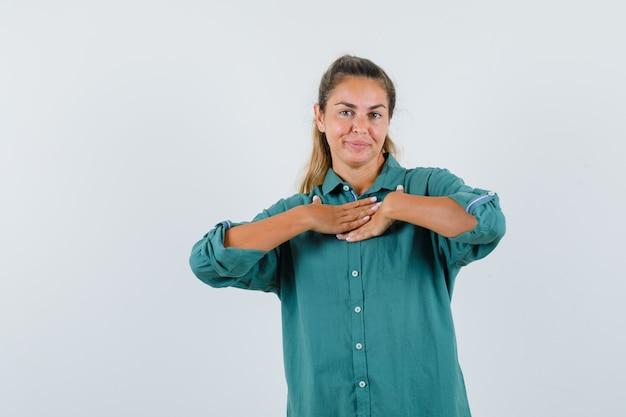 Junge frau, die hand auf brust in grüner bluse ruht und glücklich schaut