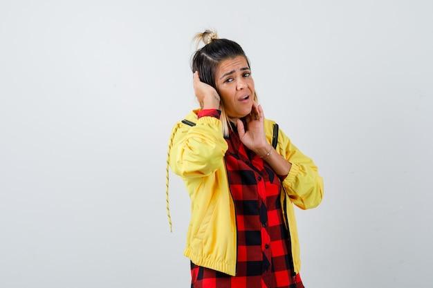 Junge frau, die hand auf dem kopf hält, während sie die wange mit den fingern in kariertem hemd, jacke berührt und beunruhigt aussieht. vorderansicht.