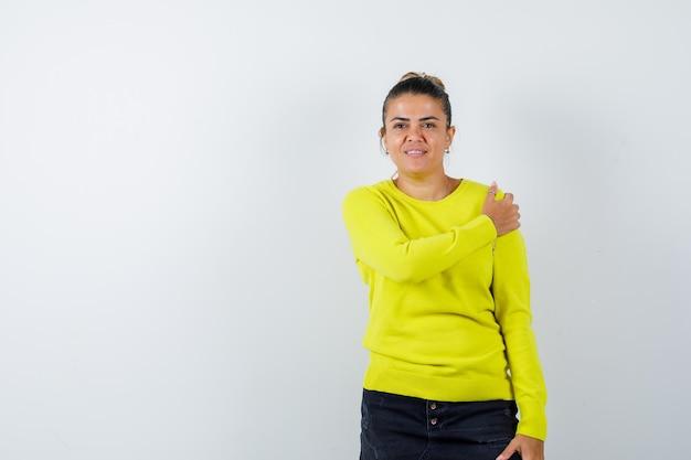 Junge frau, die hand auf der schulter in pullover, jeansrock hält und selbstbewusst aussieht