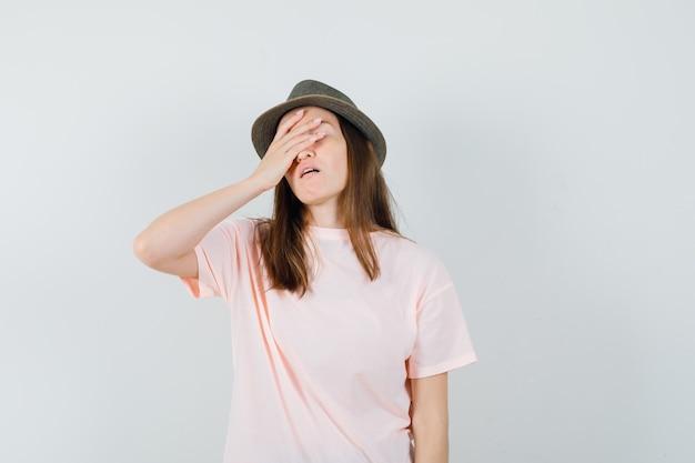 Junge frau, die hand auf gesicht in rosa t-shirt, hut hält und vergesslich schaut. vorderansicht.