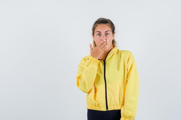 Junge frau, die hand auf ihrem mund im gelben regenmantel hält und überrascht schaut