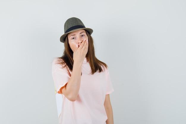 Junge frau, die hand auf mund im rosa t-shirt, hut hält und überrascht schaut, vorderansicht.