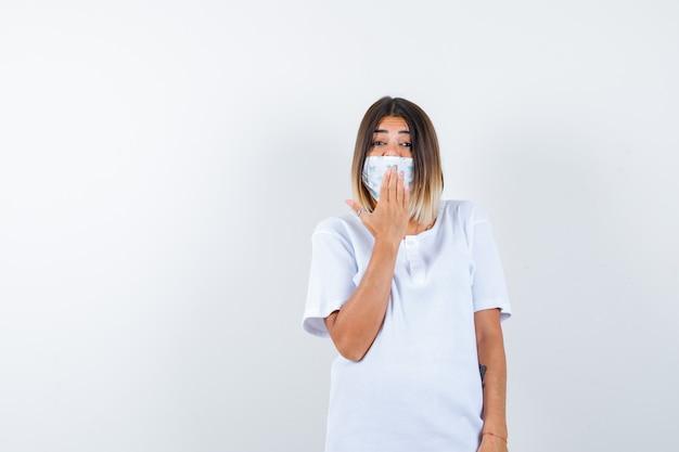 Junge frau, die hand auf mund im t-shirt, in der maske hält und fröhlich, vorderansicht schaut.