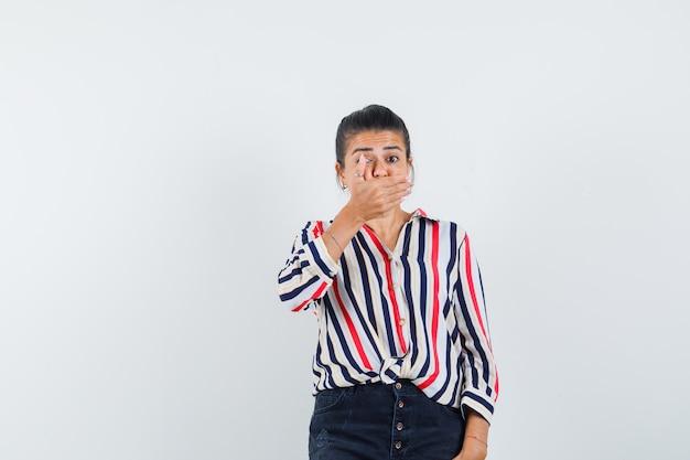 Junge frau, die hand auf mund in gestreifter bluse setzt und überrascht schaut.